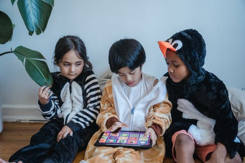Kids in Costumes Playing Games with Tablet Computer