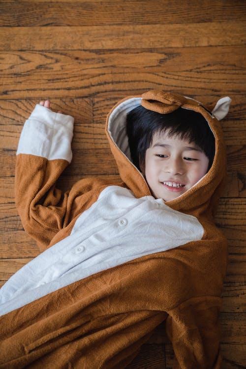 Boy in Brown Animal Costume Lying on Wooden Floor