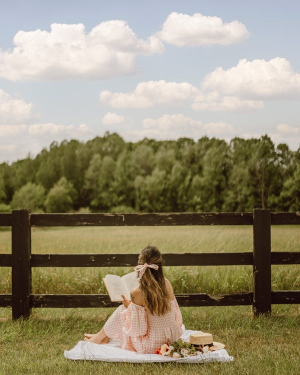 Back View of a Woman Reading a Book while Sitting on a Picnic Blanket near the Wooden Fence