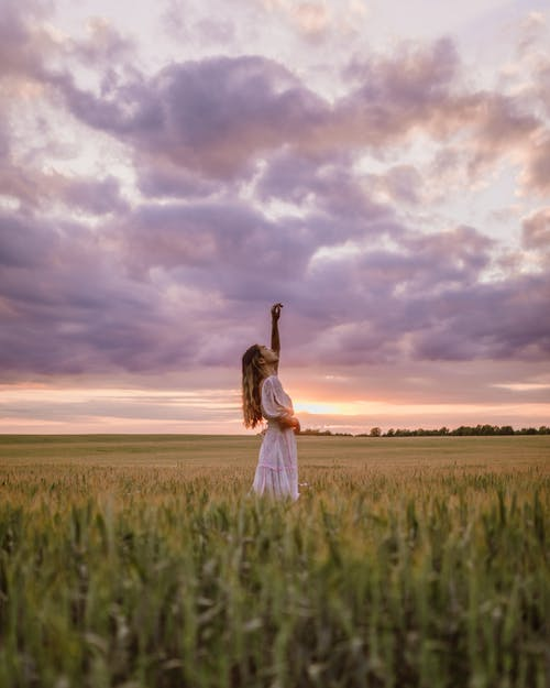 Woman in White Dress Standing in Field With Raised Hand