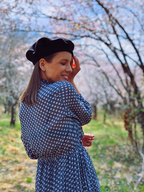 Woman in Blue and White Polka Dot Long Sleeve Shirt and Black Knit Cap Standing Near the Trees