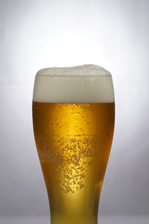 Clear Drinking Glass With Beer and Foam