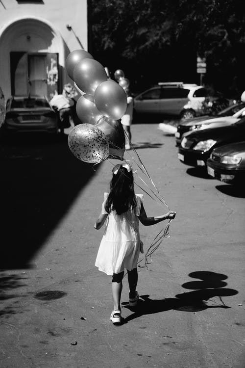Girl in White Dree Walking with Balloons in Her Hand