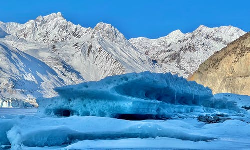 Glacier Beside Snow Covered Mountains