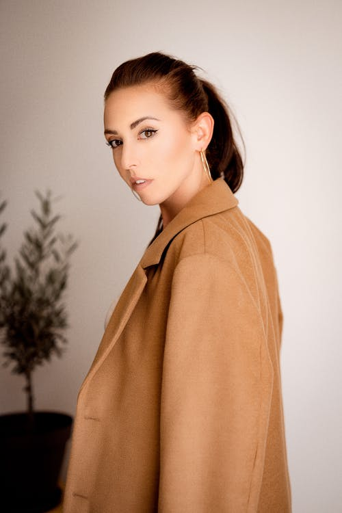Woman in Brown Coat Standing Near Green Plant