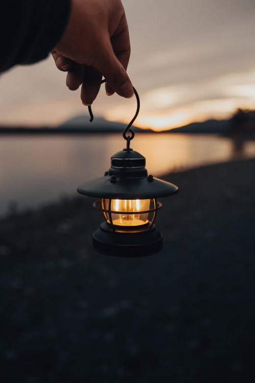 Close-Up Shot of a Person Holding a Small Lighted Lantern