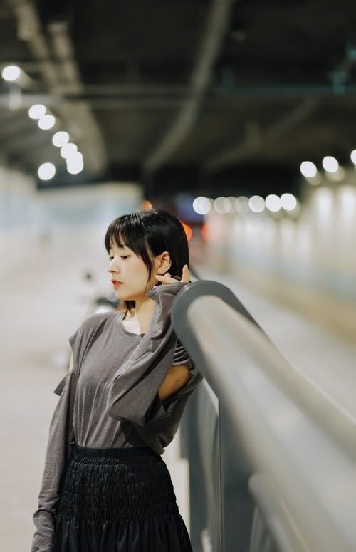 A Pretty Woman in Gray Long Sleeves Leaning on a Metal Railing