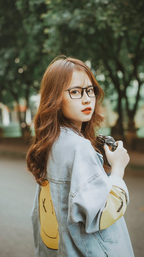 A Pretty Woman in Denim Jacket and with Eyeglasses Standing