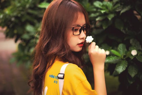 Close-Up Shot of a Pretty Woman with Eyeglasses Smelling a White Flower