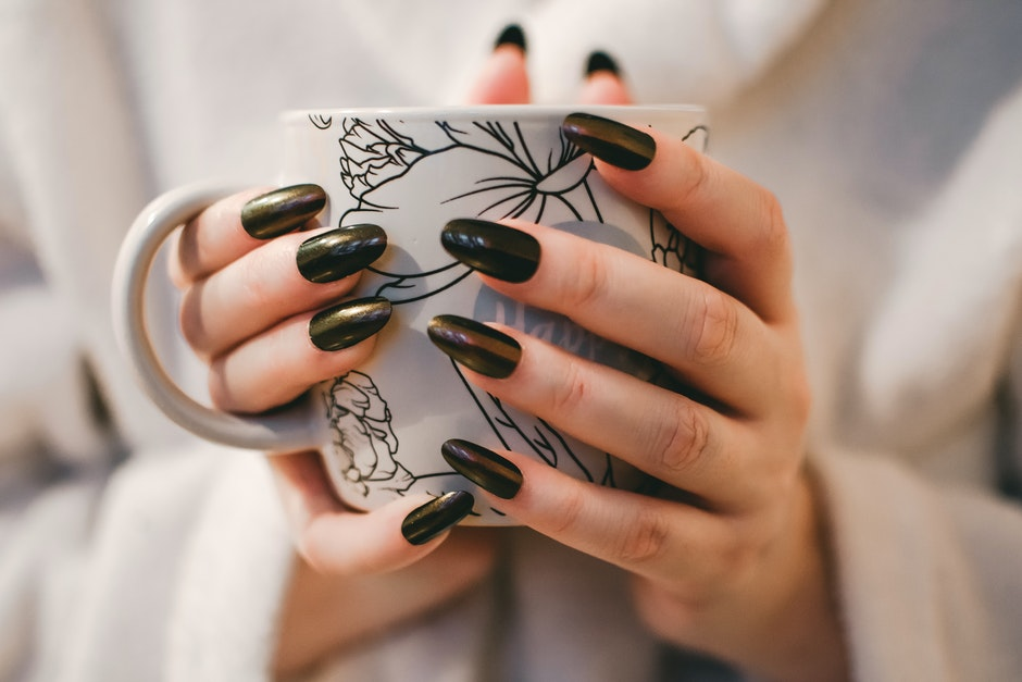 Woman With Black Manicure Holding White and Grey Floral Ceramic Cup