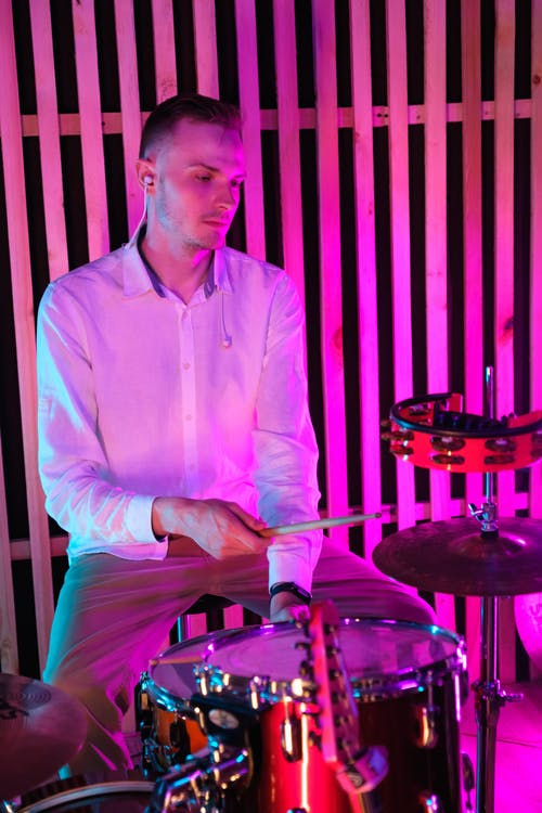 Photo of a Man in a White Dress Shirt Playing the Drums
