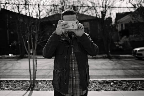Black and white shot of faceless man in casual clothes standing on pavement and taking photo on smartphone
