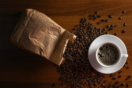 A Cup of Coffee Near a Paper Bag With Roasted Coffee Beans
