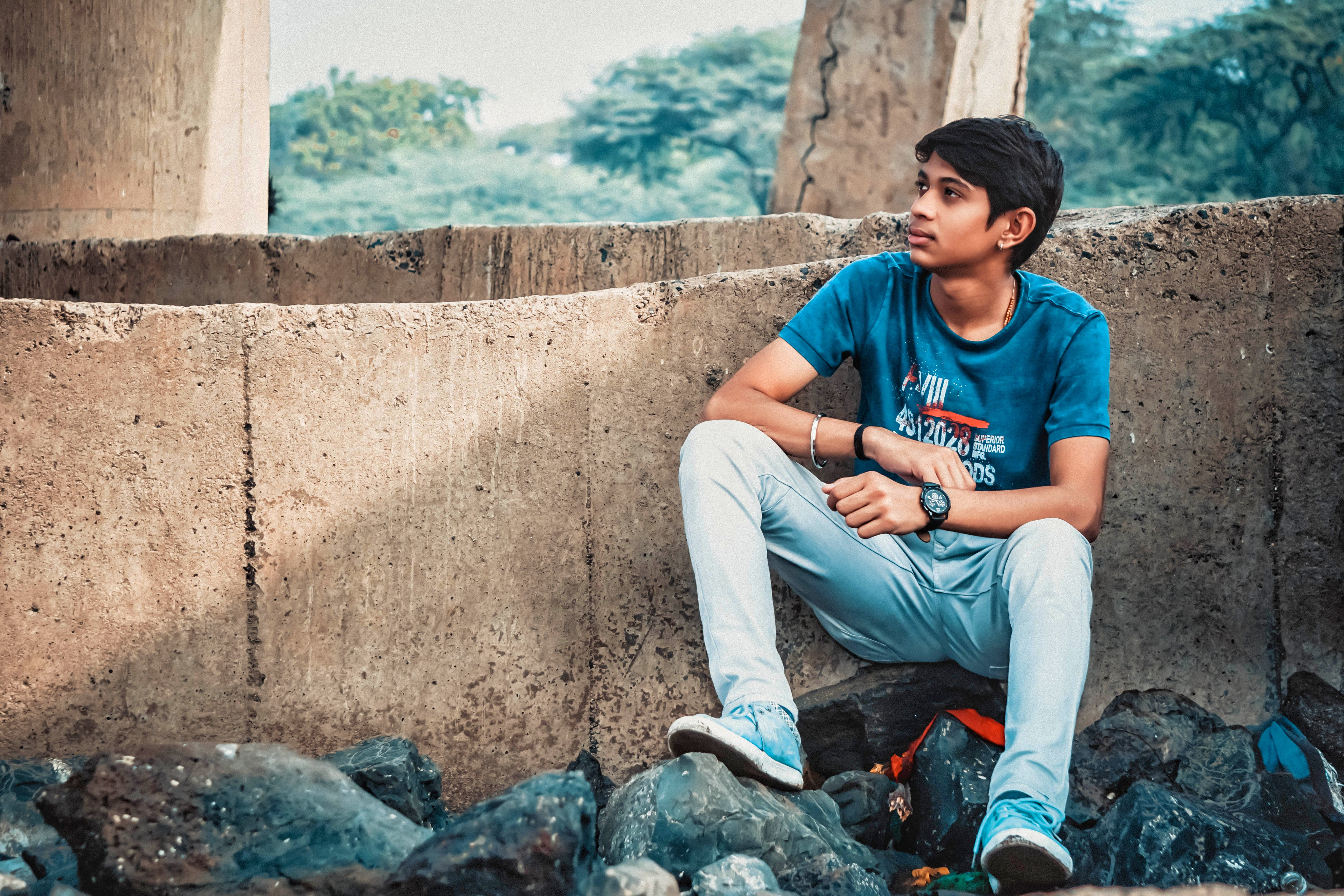 Man Sitting on Stone Leaning on Concrete Wall