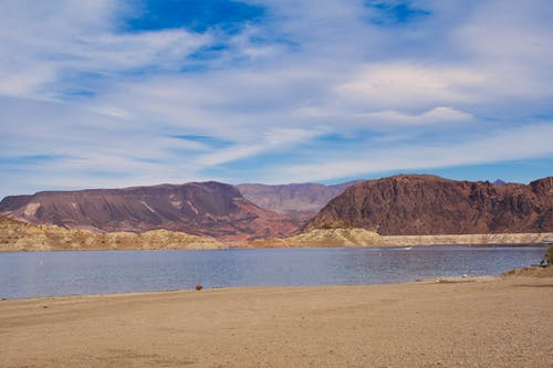 Brown Mountains Near Body of Water Under Blue Sky