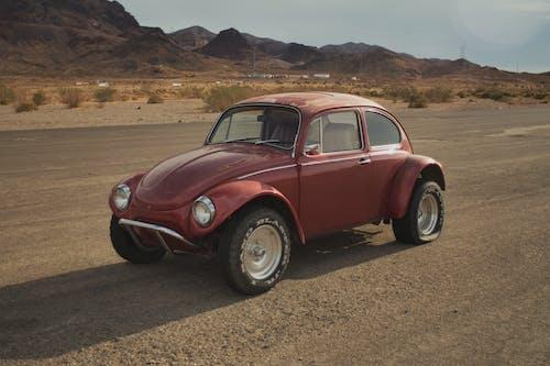Red Volkswagen Beetle on Brown Soil