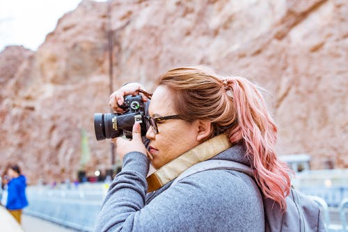 Woman Wearing Gray Jacket Using Black Dslr Camera