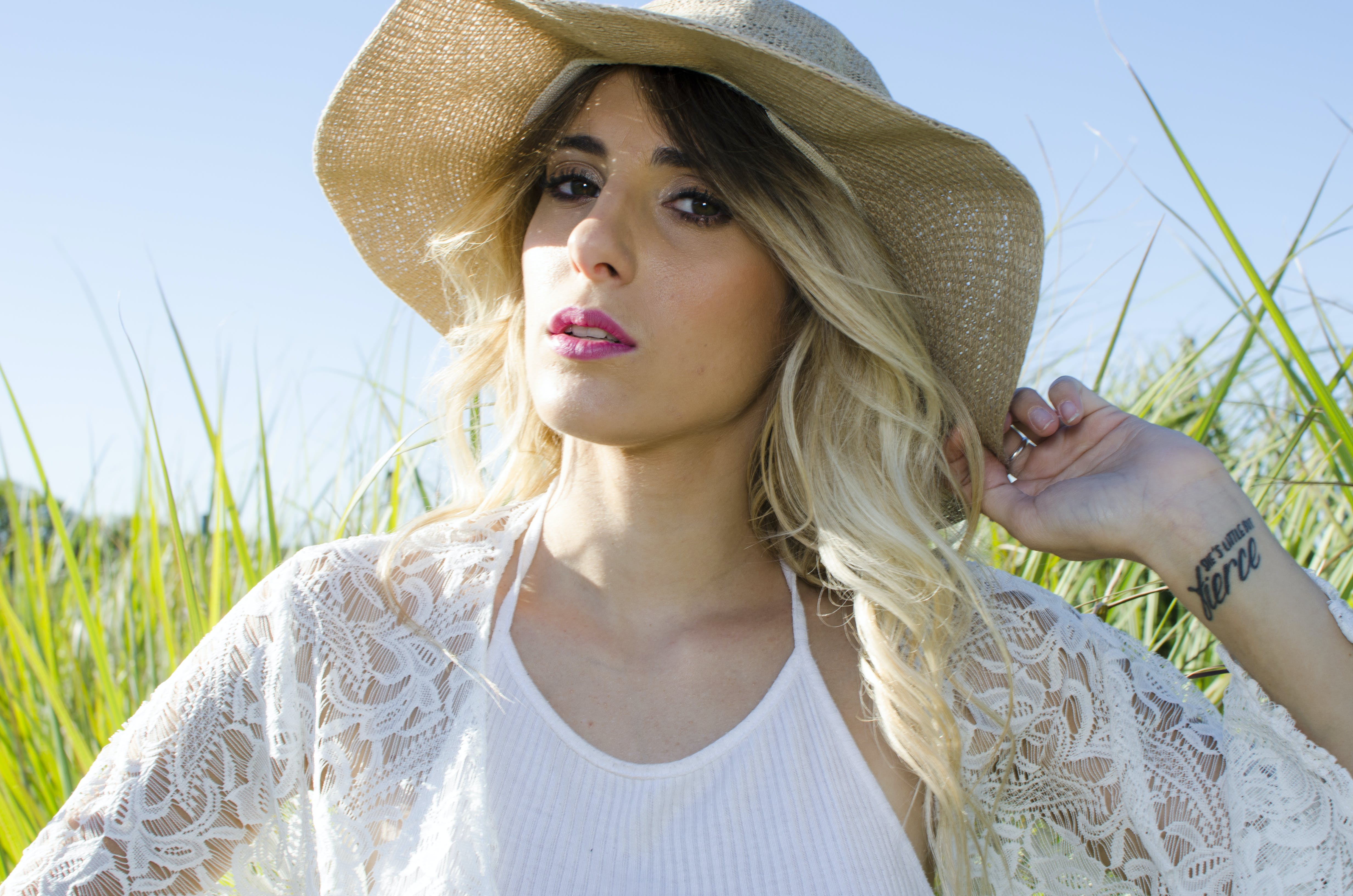 Woman Wearing Brown Hat and White Cardigan Standing in Middle of Grass Field