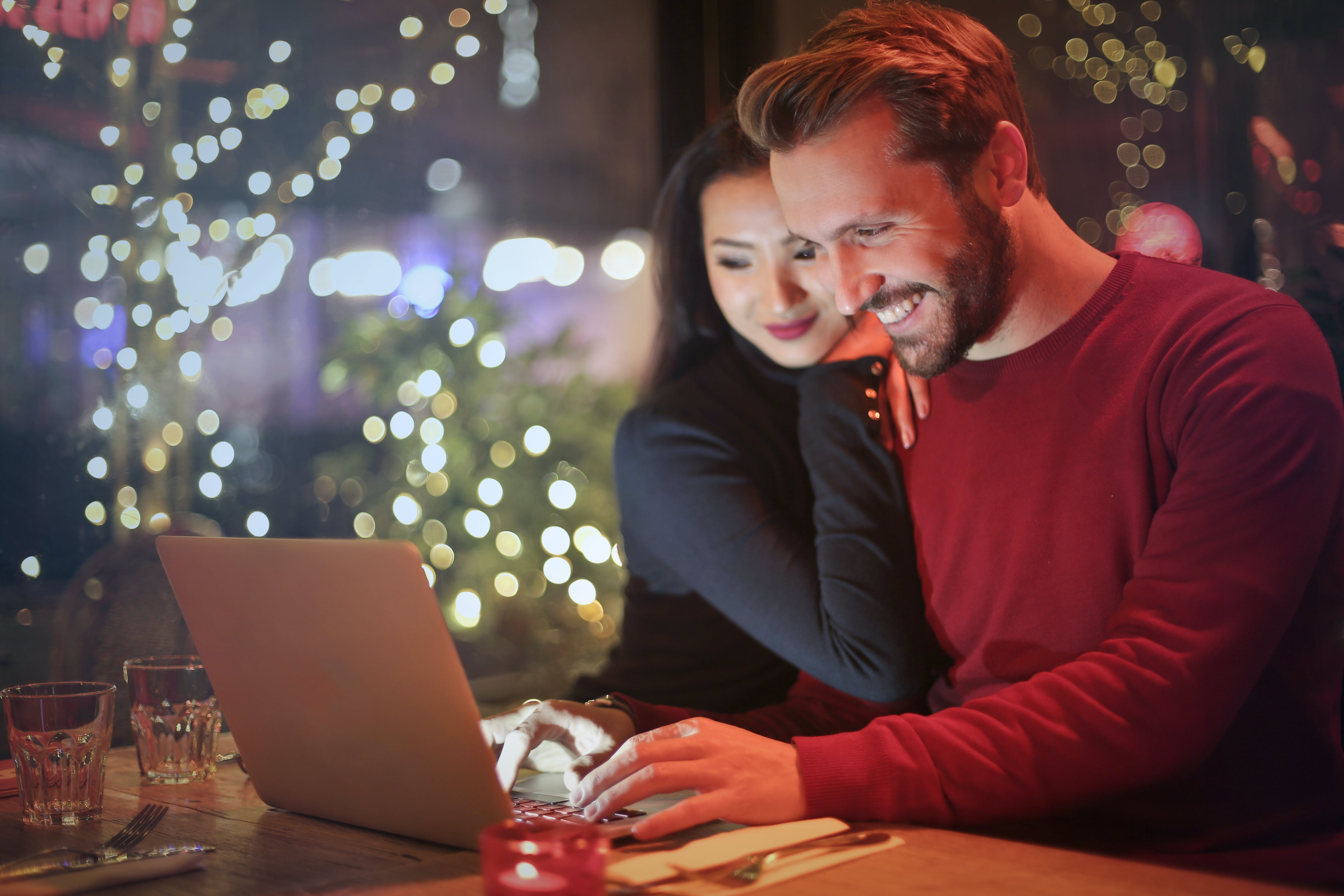 Happy man and woman behind laptop