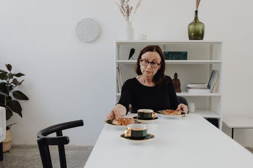 A Sad Woman in Black Long Sleeves Sitting while Looking at the Food on the Table