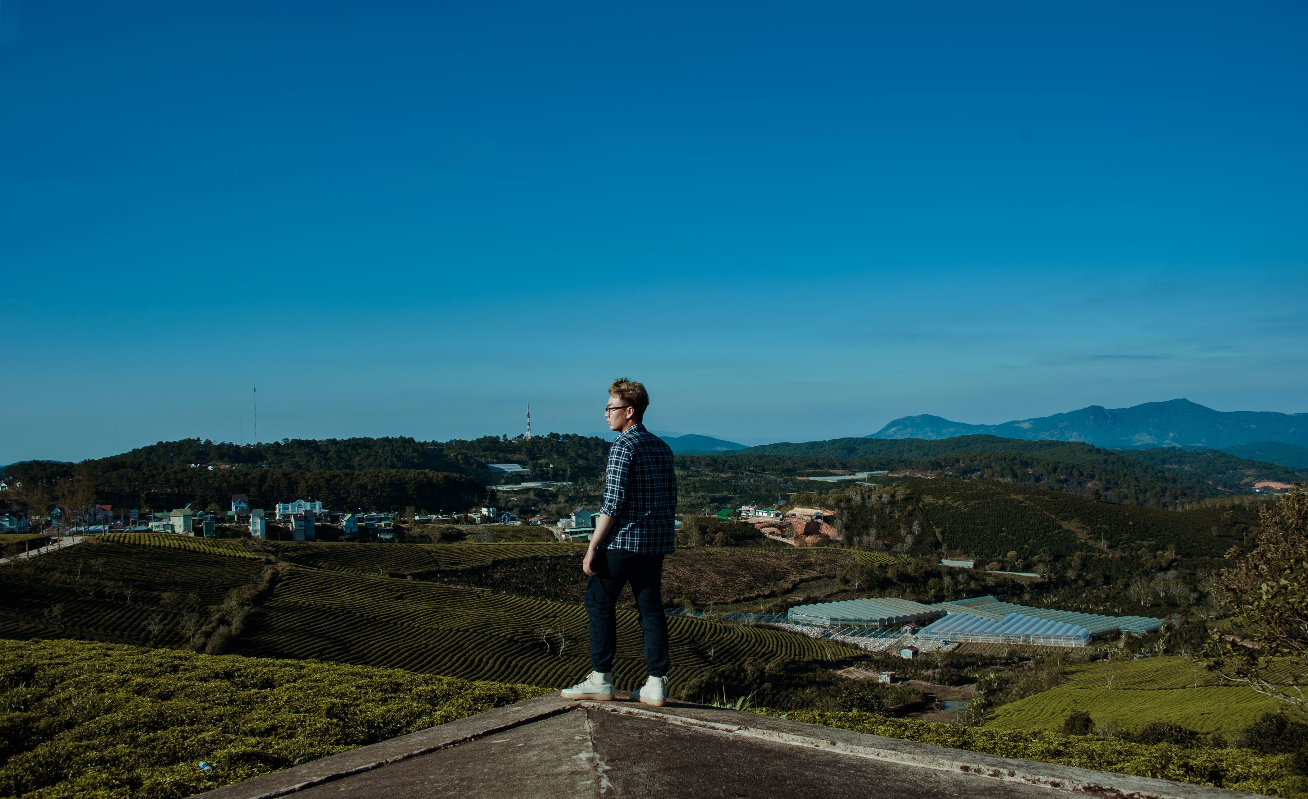 Man Wearing Blue and Gray Gingham Dress Shirt Standing in Green Grass Field