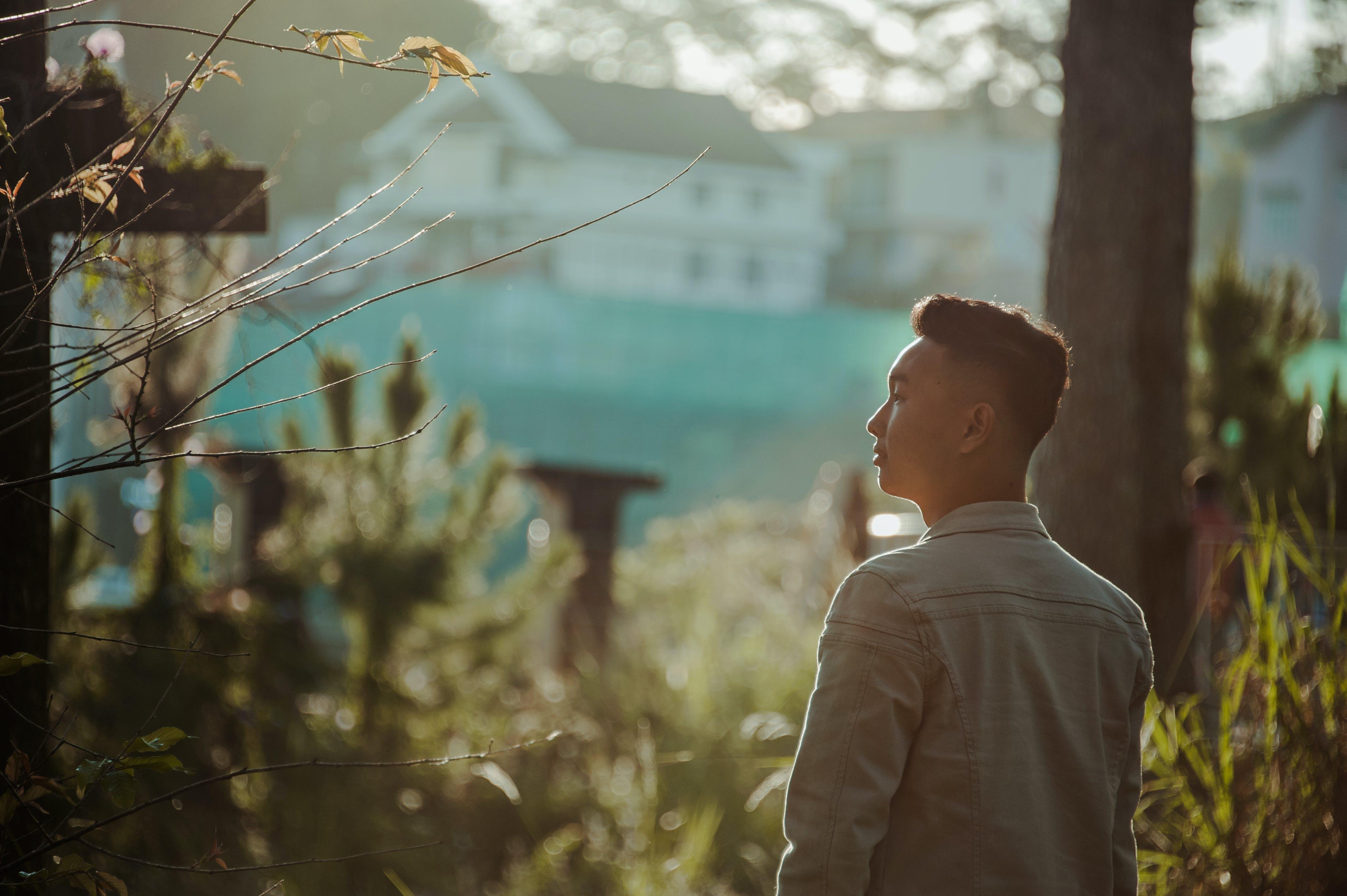 Man Wearing Gray Dress Shirt Standing Near Green Leaf Plant