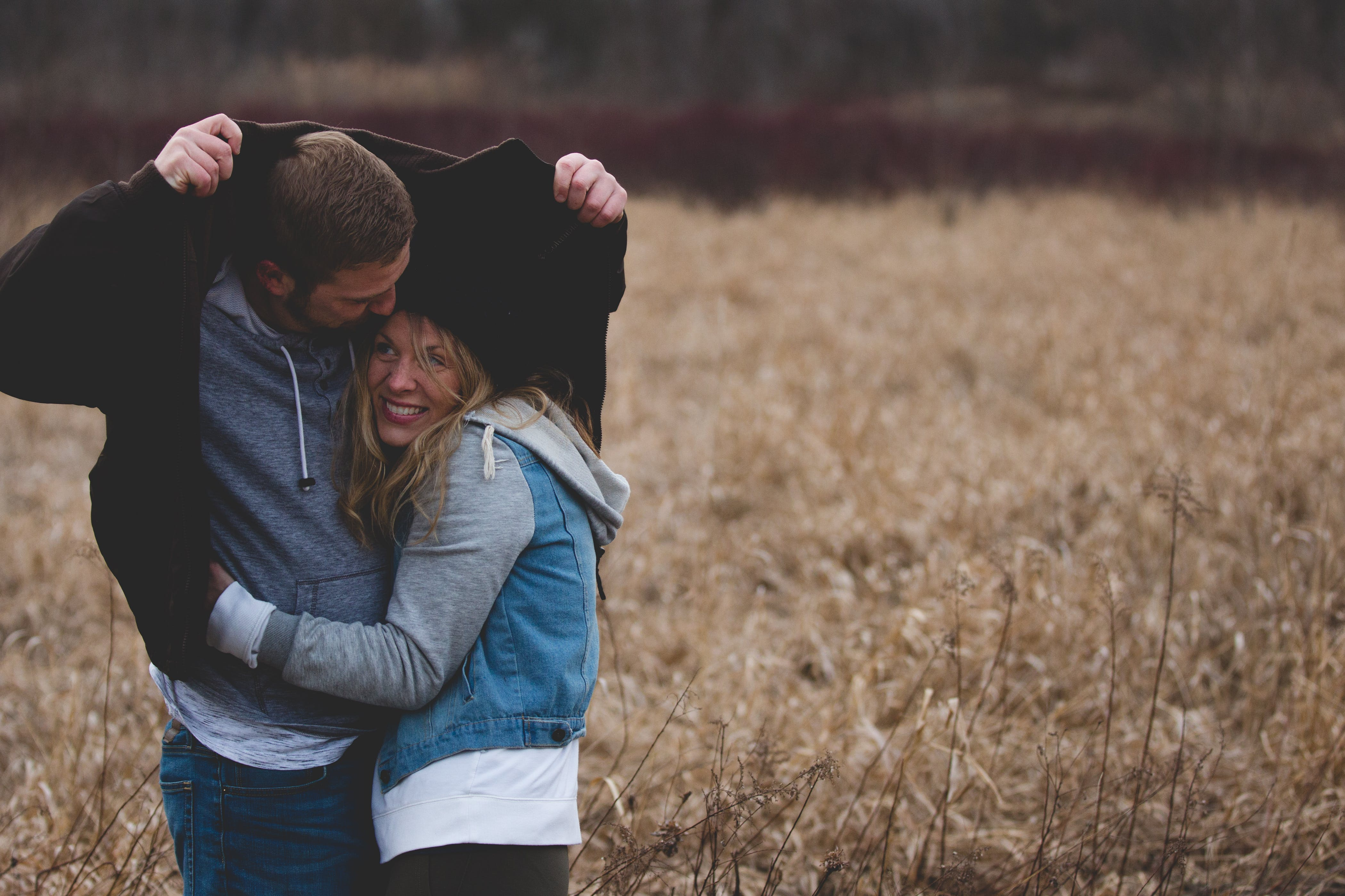 Man and Woman Hugging on Brown Field