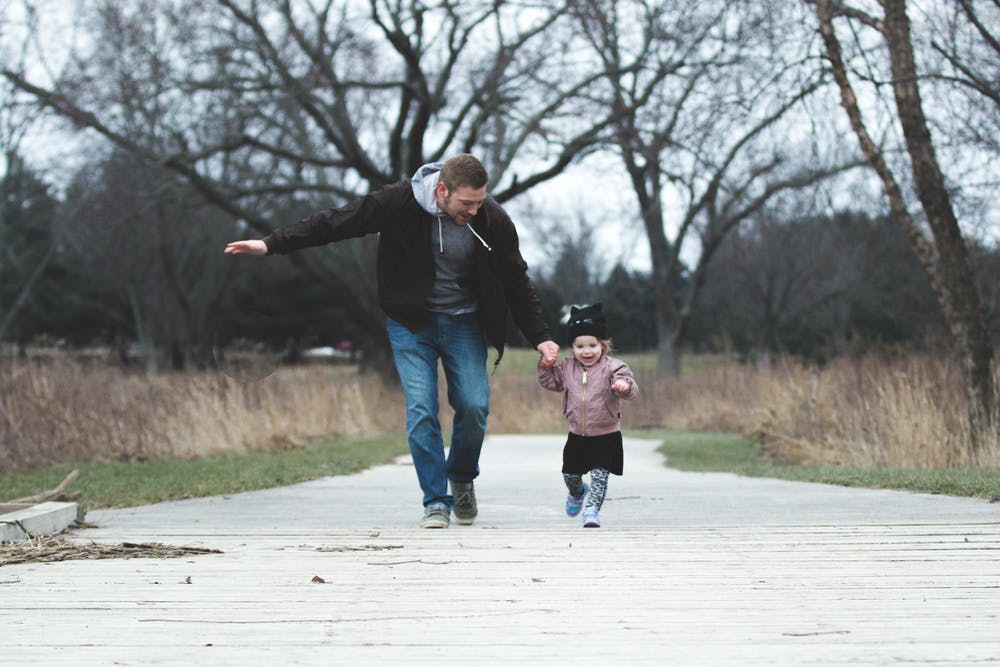 Father and daughter running on asphalt road | Photo: Pexels