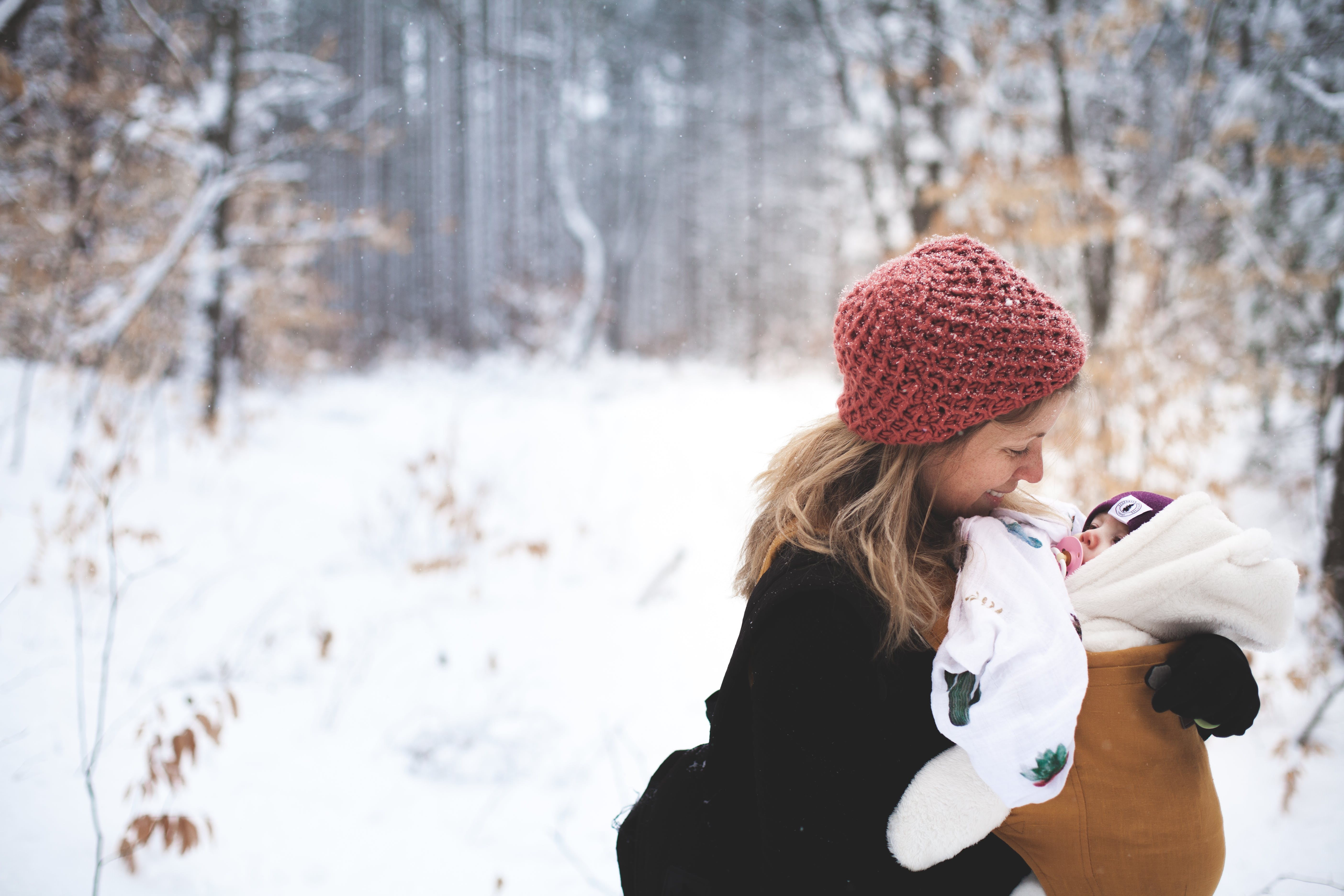 Woman in Red Knitted Cap and Black Top Holding Baby With Brown Carrier