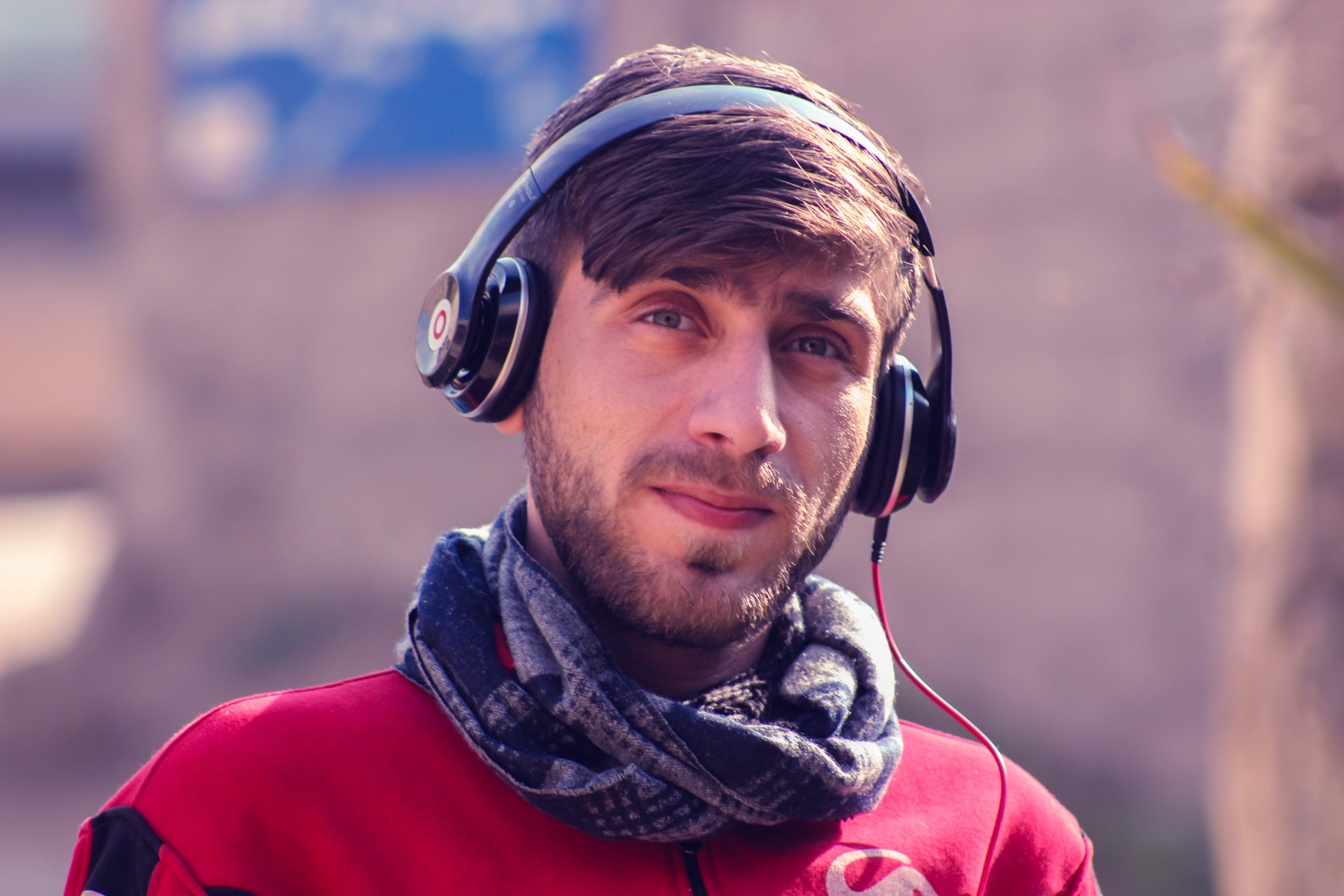 Closeup Photo of a Man Wearing Red Top, Gray Scarf, and Black Beats by Dr. Dre Headphones