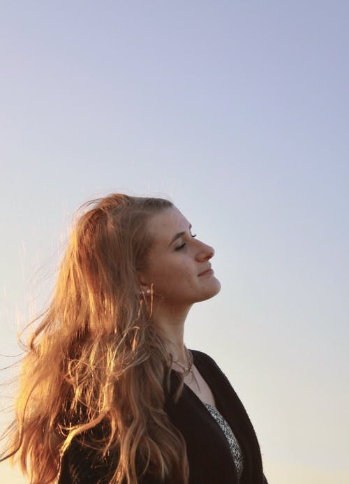 Woman with Messy Hair Under Blue Sky