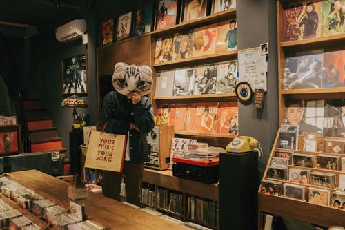 Person in Music Store with Cat Head Mask