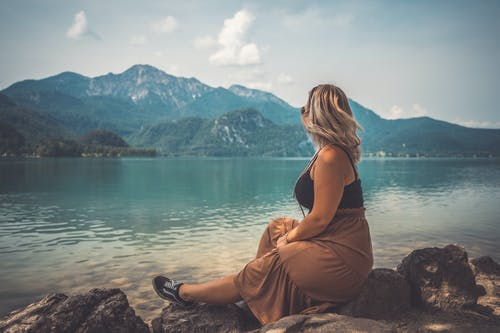 Woman in Black Tank Top and Brown Pants Sitting on Rock Near Body of Water during