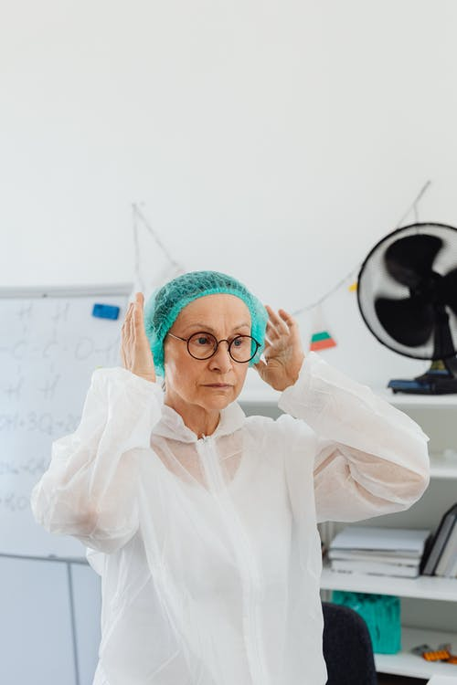 Woman Wearing Bouffant Cap and Isolation Gown