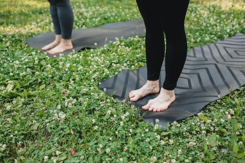 Person in Black Pants Standing on Black Yoga Mat