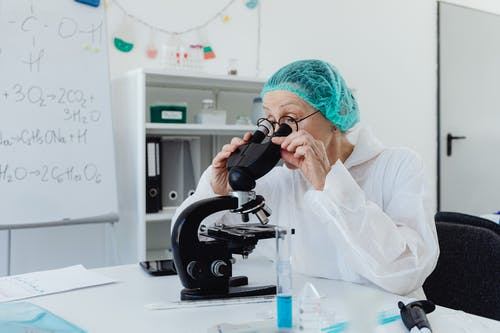 Woman with Eyeglasses Looking through a Microscope
