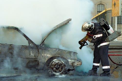 A Firefighter Extinguishing a Broken Car