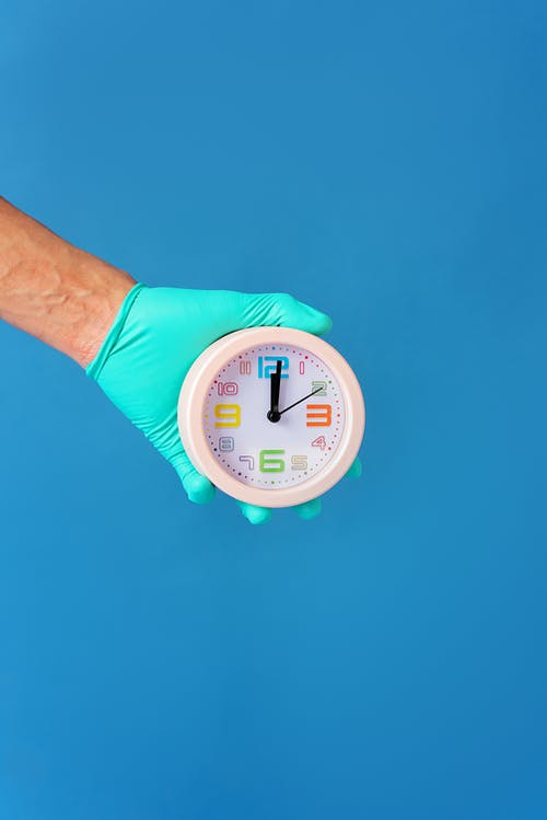 Person With Glove Holding An Alarm Clock