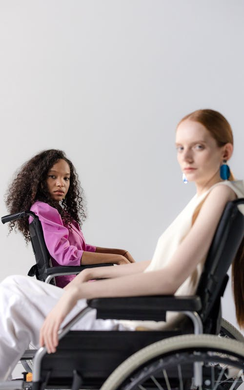 Two Women Sitting On Wheelchairs