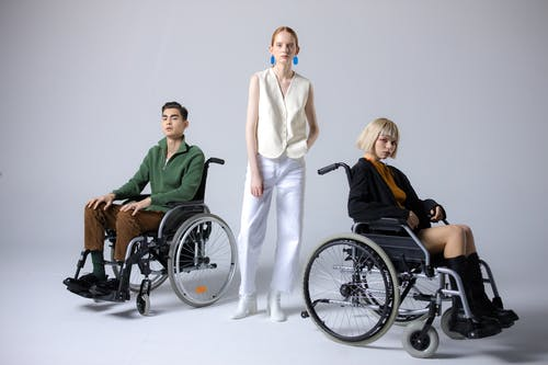 Woman Standing Beside A Man and A Woman In Wheelchairs