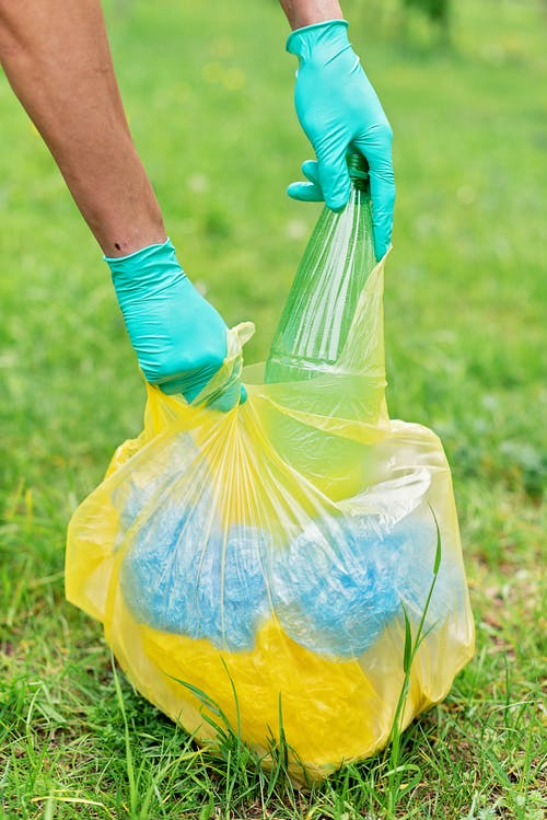 Person in Gloves Holding Yellow Plastic Bag With Recyclable Materials