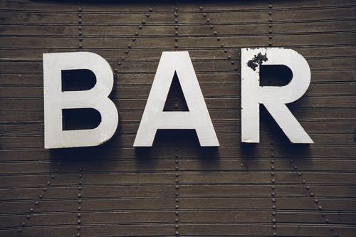 Old Bar Sign On A Wooden Wall