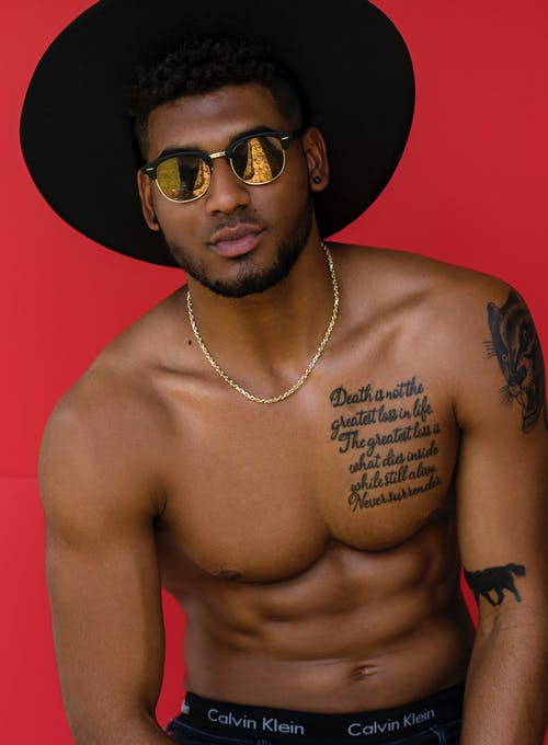 Topless Man Wearing Black Sunglasses and Black Hat