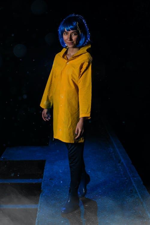 Woman in Yellow Coat Standing on Blue Floor
