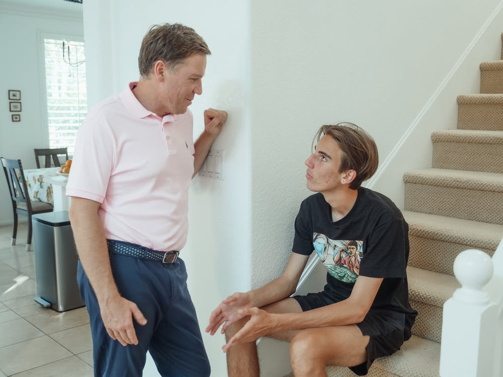 Man standing talking to teenage son on the stairs