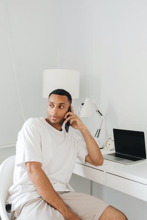 Man in White Crew Neck T-shirt Sitting on White Chair