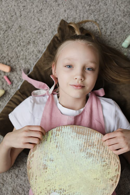 Girl in Pink and White Shirt Holding Brown Round Cardboard