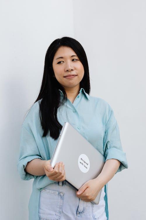 Woman Holding a Gray Laptop
