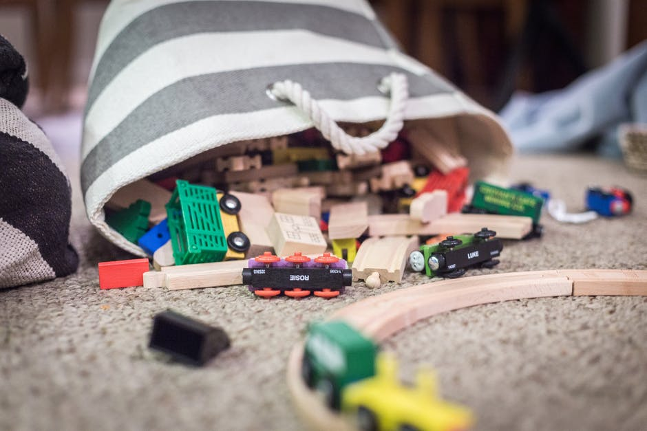 Plastic Toy Car Scattered on Brown Textile