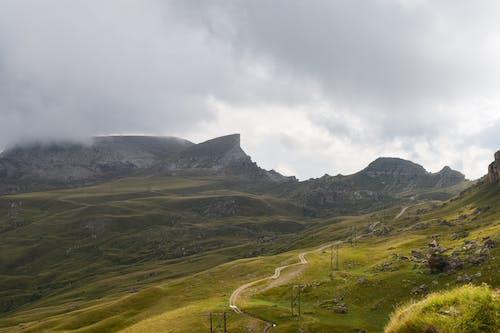 Green  Grass Field on Rocky Hill Under Gray Clouds